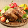 Whole roasted chicken with vegetables on plate, on wooden table - Stock Photo