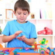 Cute little boy moulds from plasticine on table — Stock Photo #19447525