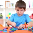 Cute little boy moulds from plasticine on table — Stock Photo #19447527