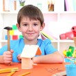 Cute little boy makes birdhouse for birds — Stock Photo #19447549