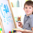 Little boy painting paints picture on easel — Stock Photo #19447573