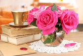 Beautiful pink roses in vase on wooden table on room background — Stock Photo