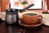 Cup of coffee with scarf and coffee maker on table in room — Stock Photo