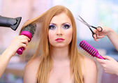 Beautiful woman and hands with brushes, scissors and hairdryer in beauty salon — Stock Photo