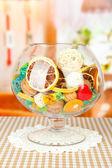 Secchi arance, palle di vimini e altre decorazioni casa in ciotola di vetro, su sfondo luminoso — Foto Stock