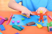 Child moulds from plasticine on table — Stock Photo