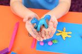 Child's hands holding hand-made plasticine hourse over desk — Stock Photo