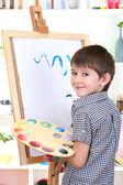 Garotinho imagens de tintas de pintura em cavalete — Foto Stock