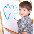 Little boy painting paints picture on easel — Stock Photo #19471639
