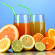 Lots ripe citrus with juices on blue background - Foto Stock