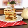 Sweet pancakes on plate with condensed milk on table in room — Stock Photo