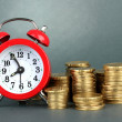 Alarm clock with coins on grey background — Foto Stock