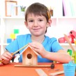 Cute little boy makes birdhouse for birds - Stock Photo