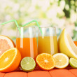Lots ripe citrus with juices on wooden table on natural background - Foto Stock