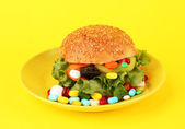 Conceptual image for nutritional care:assorted vitamins and nutritional supplements in bun.On color background — Stock Photo