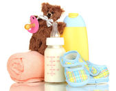 Bottle of milk, pacifier and baby cosmetic with towel isolated on white — Stock Photo