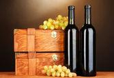 Houten gevallen met wijn flessen op houten tafel op bruine achtergrond — Stockfoto