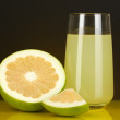 图库照片: Delicious sweetie juice in glass and sweetie next to it on dark orange background