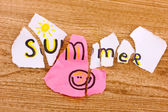 Torn paper with words Summer close-up on wooden table — Stock Photo