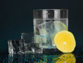 Ice cubes in glass with lemon on dark blue background — Stock Photo