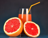 Delicious grapefruit juice in glass and grapefruit next to it on dark blue background — Stock Photo