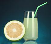 вкусная конфетка сок в стакан и конфетка рядом с ним на синем фоне — Стоковое фото