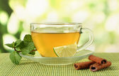 Cup of tea with mint,lime and cinnamon on table on bright background — Stock Photo