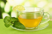 Cup of tea with mint on table on bright background — Stock Photo