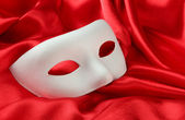 White mask, on red silk fabric — Stock Photo