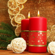 Two candles and christmas decorations, on golden background — Stock Photo
