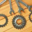 Metal cogwheels and spanners on wooden background — Стоковая фотография