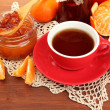 Light breakfast with tea and homemade jam, on wooden table - Stock Photo