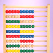 Royalty-Free Stock Photo: Bright wooden toy abacus, on purple background