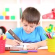 Royalty-Free Stock Photo: Cute little boy drawing in his album
