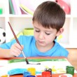 Cute little boy painting in his album - Stock Photo