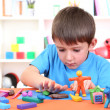 Cute little boy moulds from plasticine on table - Stok fotoğraf