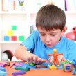 Cute little boy moulds from plasticine on table - Foto Stock