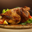 Whole roasted chicken with vegetables, on wooden table, on brown background — Stockfoto