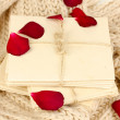 Stock Photo: Stacks of old letters with dried rose petals on soft scarf