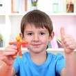 Cute little boy moulds from plasticine on table - Stock Photo