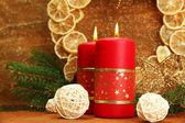 Twee kaarsen en kerstversiering, op gouden achtergrond — Stockfoto