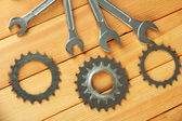 Metal cogwheels and spanners on wooden background — Stockfoto