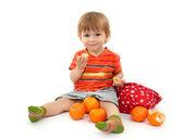 Süße kleine junge essen mandarinen, isoliert auf weiss — Stockfoto