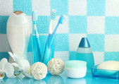 Bath accessories on shelf in bathroom on blue tile wall background — Zdjęcie stockowe