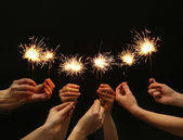 Beautiful sparklers in hands on black background — Stock Photo
