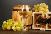 Dřevěné pouzdro s láhví vína, barel, skleničku a hroznů na dřevěný stůl na šedém pozadí — Stock fotografie