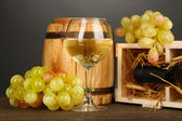 Wooden case with wine bottle, barrel, wineglass and grape on wooden table on grey background — Zdjęcie stockowe