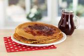 Zoete pannenkoeken op plaat met jam op tafel in de keuken — Stockfoto