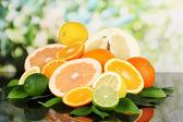 Hodně zralé citrusy na černém stole na přírodní pozadí — Stock fotografie