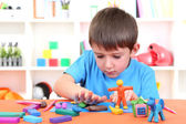 Cute little boy moulds from plasticine on table — Stock Photo